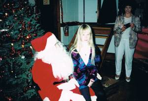 She doesn't look too happy to be on Santa's lap, does she?
