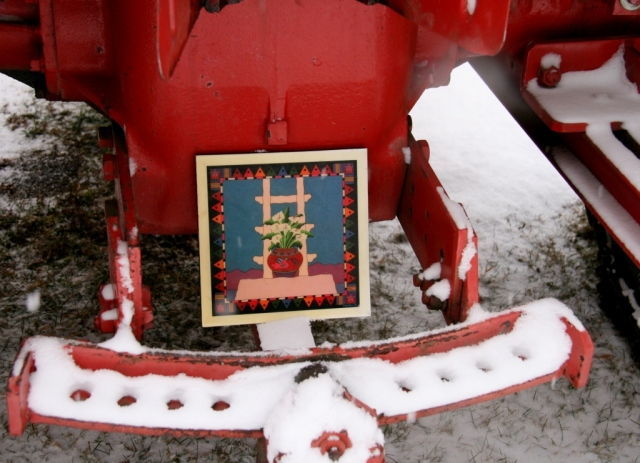 Native American art tile on snowplowing tractor