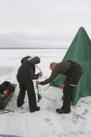 Derrick learns how to drill a hole into the ice