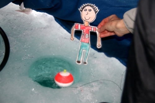 Flat Stanley checks the bobber to see if it's moving.  If so, a fish might be biting!