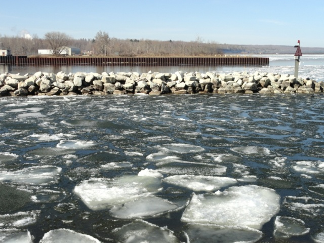 Ice floes floating behind sheltered breakwall