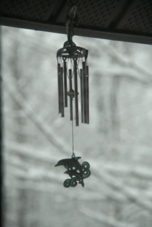 Close-up of teeny wind chime through window