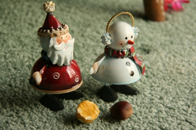A santa and snowman stole a peeled and unpeeled chestnut and merrily ran off with them.