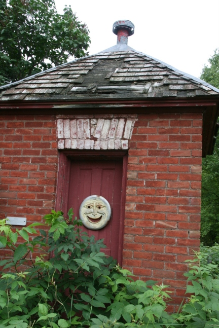 An old-time privy building (love that smiling face)