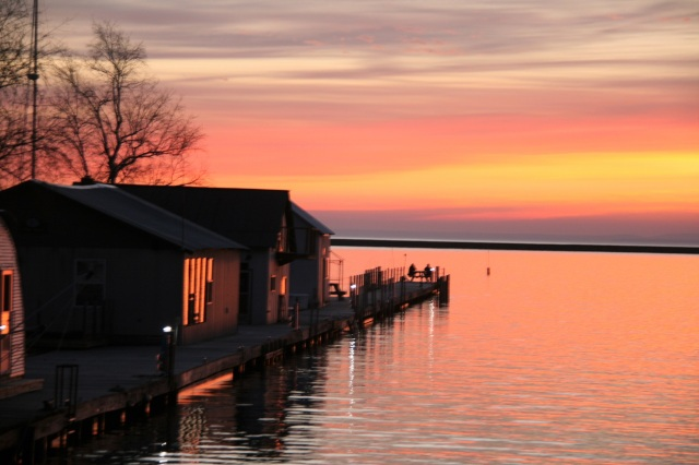 See the couple sitting at the end of the dock admiring the sunrise?