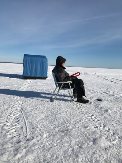 My husband sitting down ice fishing on Lake Superior